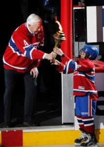 Montreal Canadiens legend Jean Beliveau passes a torch to a young skater as part the opening ceremony before the start a playoff game between between the Montreal Canadiens and Boston Bruins Monday, April 18, 2011.